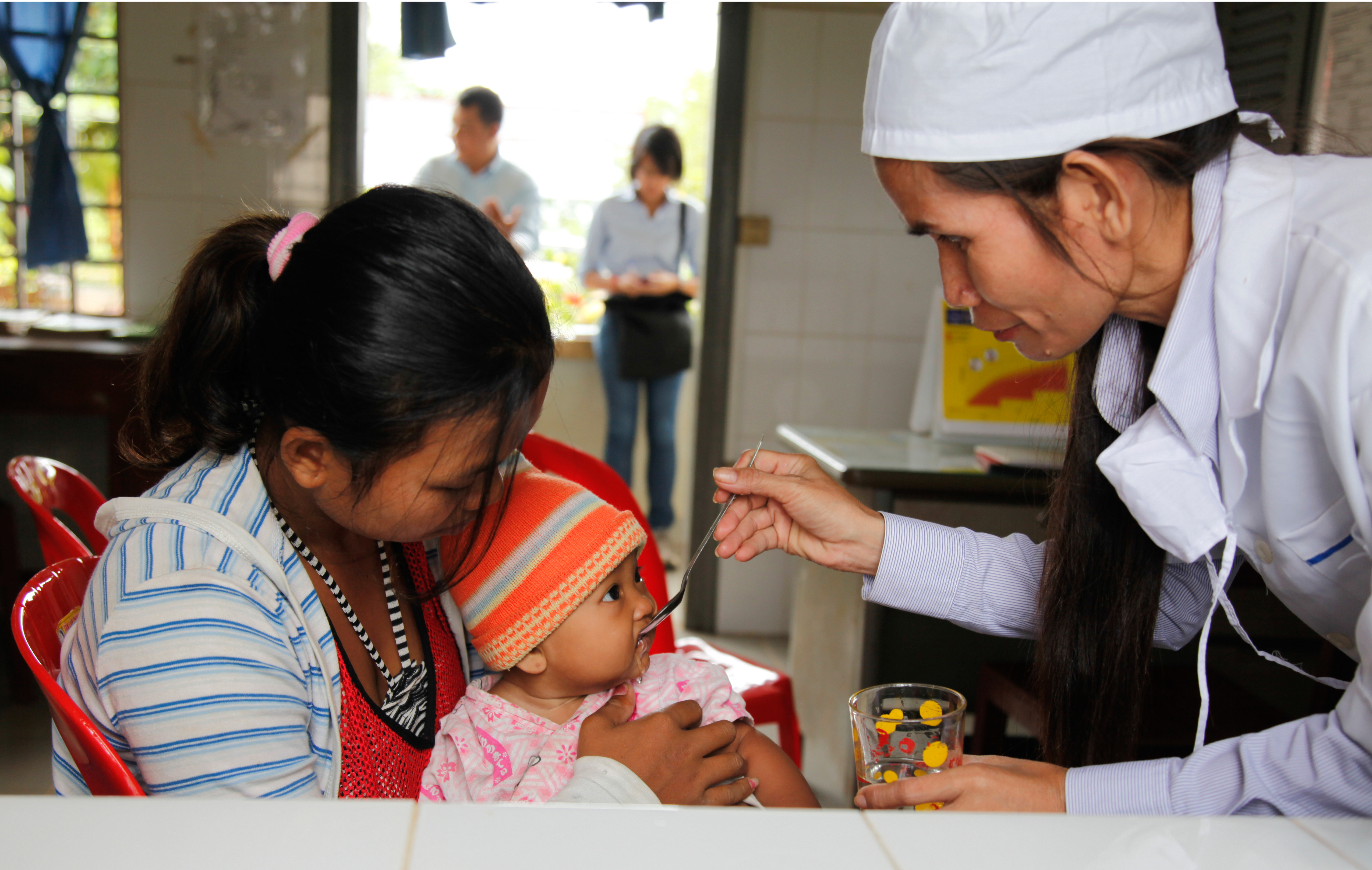 Infant girl receives oral rehydration solution (ORS) at a clinic in Cambodia.