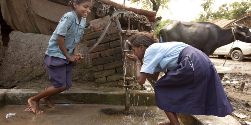 Girls pump water from a well