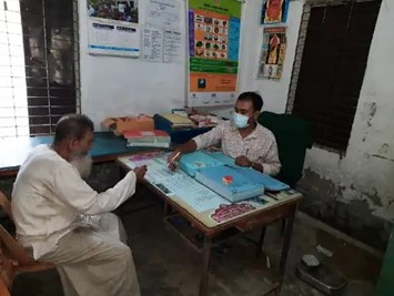 Health worker educates a community member in a health clinic in Bil Dumuria, Bangladesh