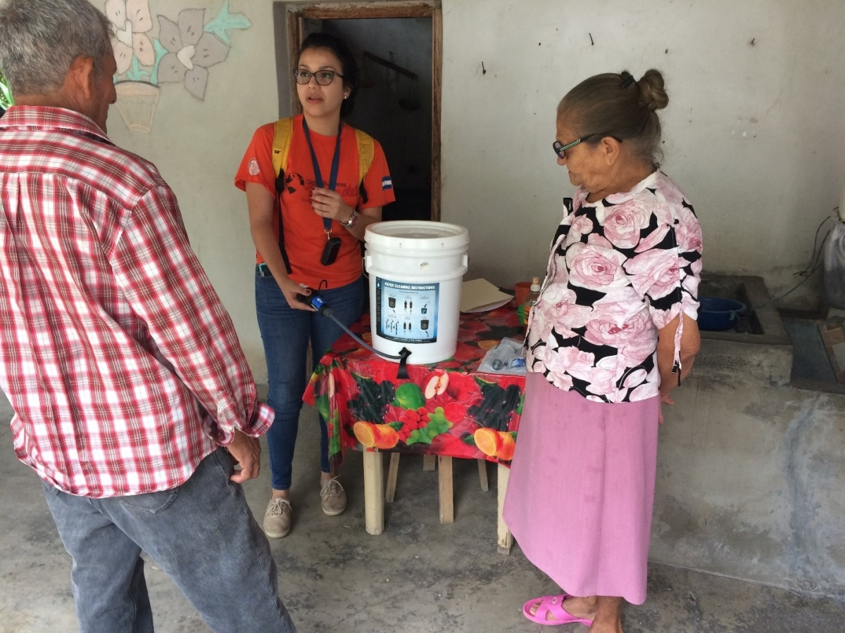 Mittchel Benitez of Global Brigades shows Don Bruno and Doña Adela how to use the water filter.