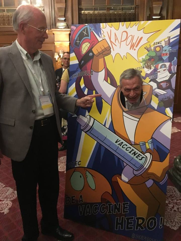Dr. Walker pointing to Dr. Bourgeois posing in a vaccine superhero cutout