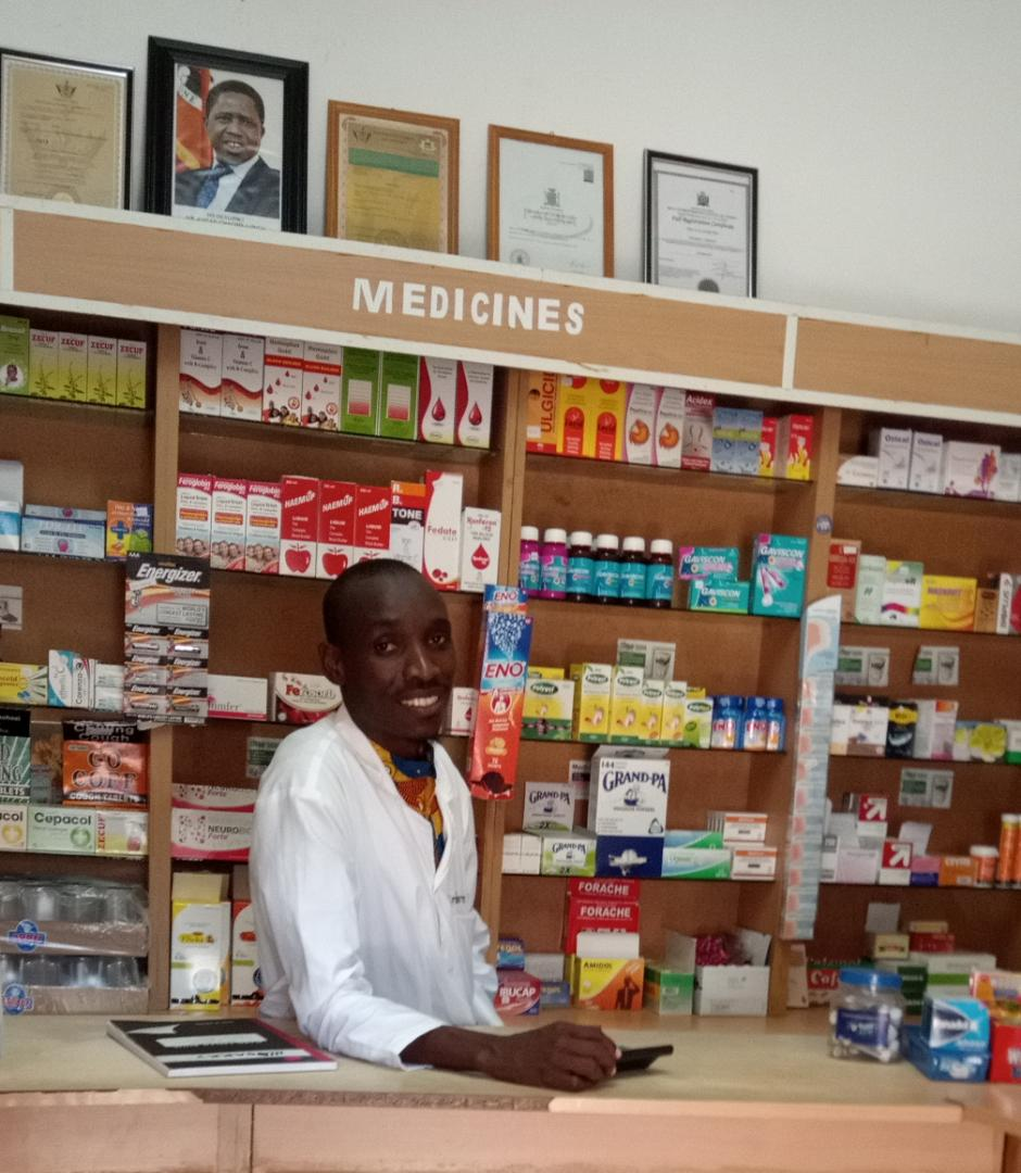 Man smiling behind a pharmacy counter