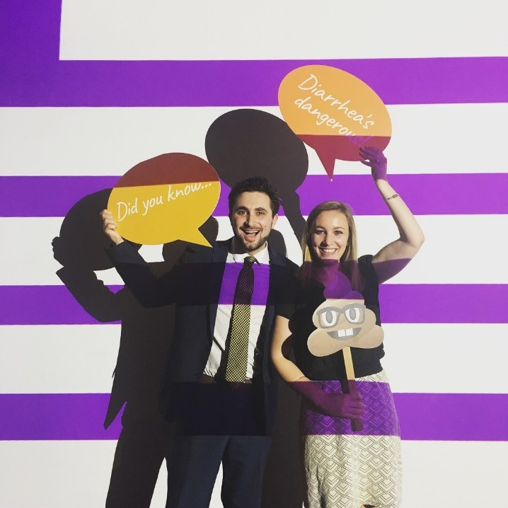 "Man and woman in front of purple and white striped wall holding poo emoji and ""Diarrhea's dangerous"" conversation bubble"