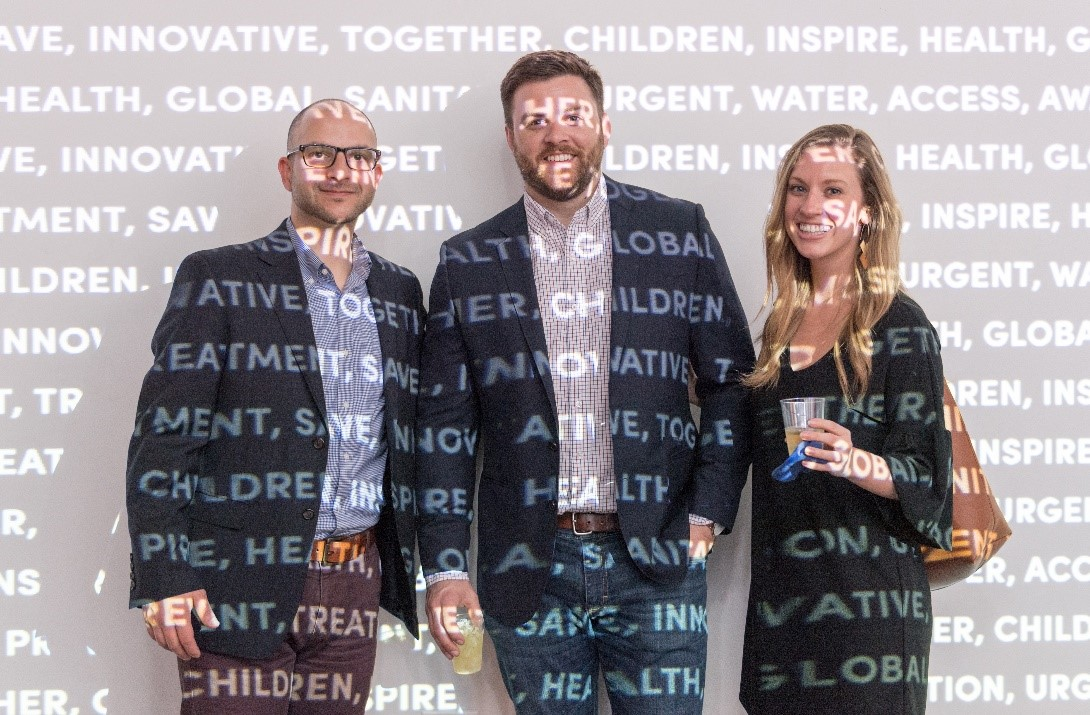 Two men and a woman covered in a wall projection of words like health, innovative, solutions