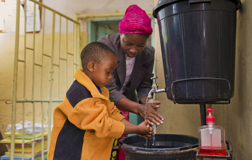 Mother and son in Zambia washing their hands together.