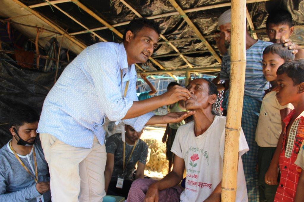 A member of icddr,b's team delivers an oral cholera vaccine to an adult male