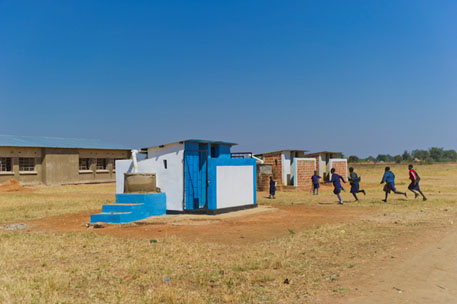Bright blue and white latrine outside of a school