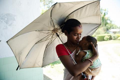 Mother holds her infant daughter after receiving routine vaccines.