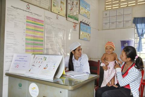 Mother holds smiling child at an ORS clinic in Cambodia.