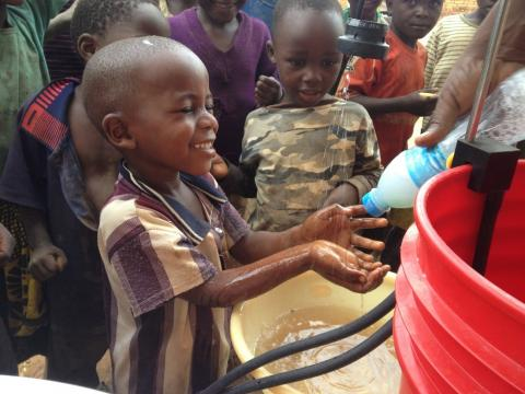 A young boy washes his hands at a handwashing station.